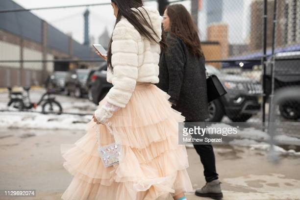 A guest is seen on the street during New York Fashion Week AW19 wearing tulle skirt and white fur coat on February 13 2019 in New York City