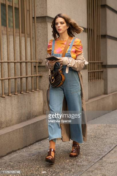 A guest is seen on the street during New York Fashion Week AW19 wearing denim overalls with orange ruffle shirt and brown heels on February 13 2019...