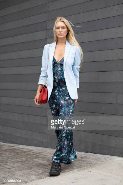 A guest is seen on the street during New York Fashion Week SS19 wearing floral pattern dress with baby blue blazer and red bag on September 8 2018 in...