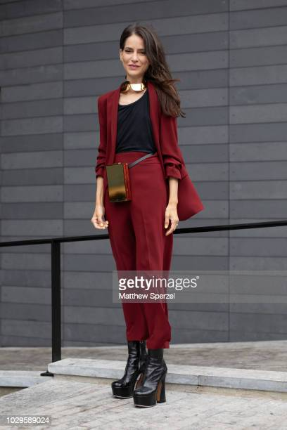 A guest is seen on the street during New York Fashion Week SS19 wearing maroon outfit with brass hip belt bag and collar on September 8 2018 in New...