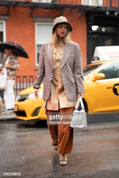A guest is seen on the street during New York Fashion Week SS19 wearing plaid blazer with tan dress and copper pants with bucket hat on September 9...