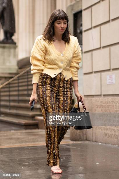 A guest is seen on the street during New York Fashion Week SS19 wearing yellow sweater with tan pattern pants on September 9 2018 in New York City