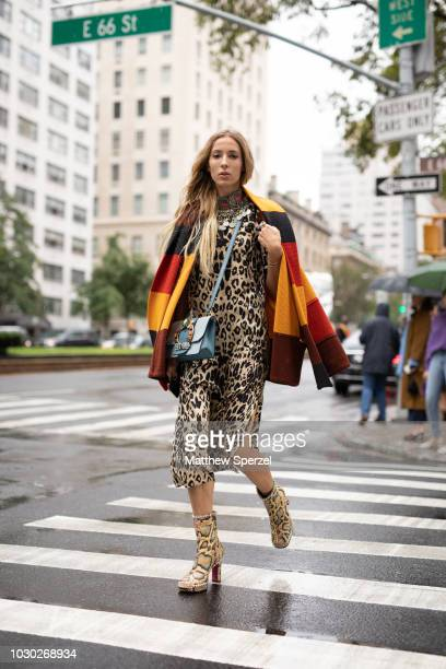 A guest is seen on the street during New York Fashion Week SS19 wearing leopard print dress and snakeskin heels on September 9 2018 in New York City