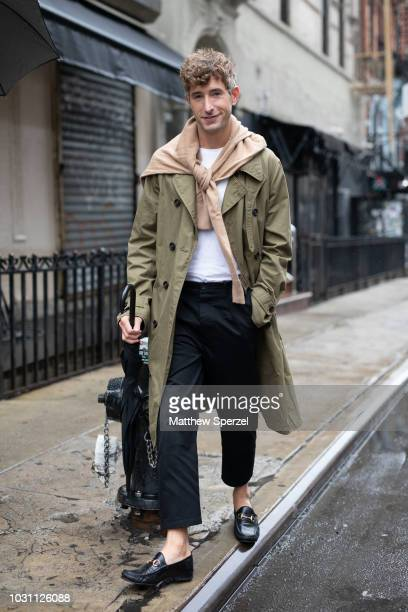 A guest is seen on the street during New York Fashion Week SS19 wearing army green coat with nude sweater and black pants on September 10 2018 in New...