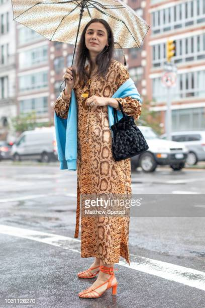 A guest is seen on the street during New York Fashion Week SS19 wearing snakeskin print dress with blue sweater on September 10 2018 in New York City