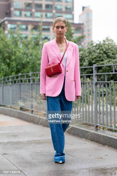 A guest is seen on the street during New York Fashion Week SS19 wearing pink blazer with blue pants and red YSL bag on September 10 2018 in New York...