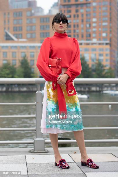 A guest is seen on the street during New York Fashion Week SS19 wearing pastel red shirt with yellow/teal sequin skirt on September 11 2018 in New...