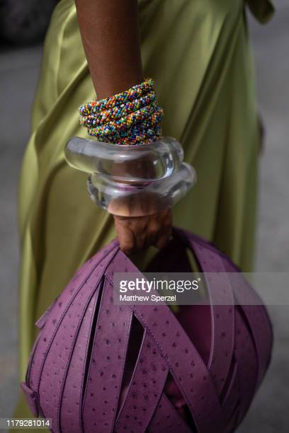 A guest is seen on the street during New York Fashion Week SS20 wearing green satin dress purple strapdesign ball bag multiple bracelets rainbow...