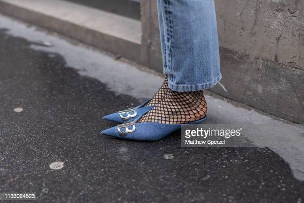 A guest is seen on the street during Paris Fashion Week AW19 wearing DB blue shoes with fishnet stockings and blue jeans on March 01 2019 in Paris...