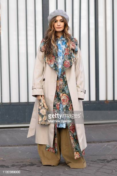 Guest is seen on the street during Paris Fashion Week AW19 wearing floral lined taupe coat, blue dress, grey beret and khaki pants on February 26,...