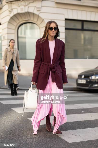 A guest is seen on the street during Paris Fashion Week AW19 wearing burgundy jacket with pink dress and white bag on February 26 2019 in Paris France