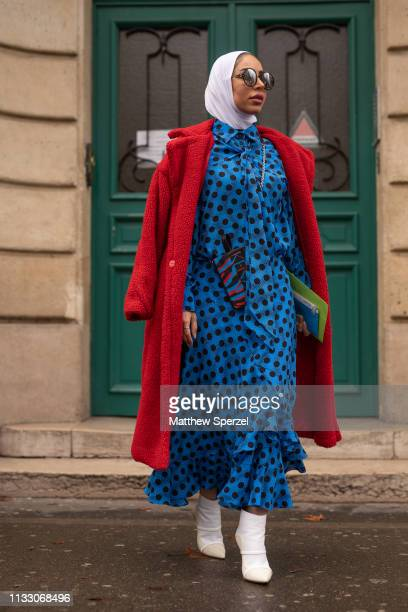 A guest is seen on the street during Paris Fashion Week AW19 wearing blue/black polka dot dress red wool coat and white hijab and shoes on March 01...