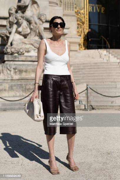 A guest is seen on the street during Paris Fashion Week Haute Couture wearing white tank top with black leather capris and taupe bag on July 02 2019...