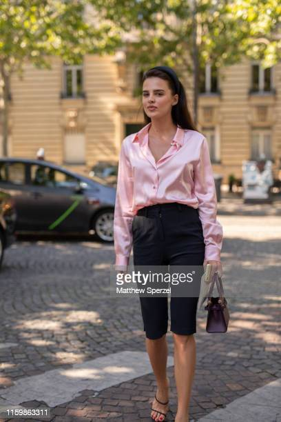 A guest is seen on the street during Paris Fashion Week Haute Couture wearing pink satin shirt with black shorts and heels on July 03 2019 in Paris...