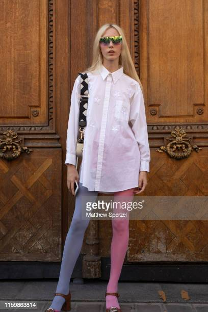 A guest is seen on the street during Paris Fashion Week Haute Couture wearing white shirt with blue/pink duotone stockings and sunglasses on July 03...