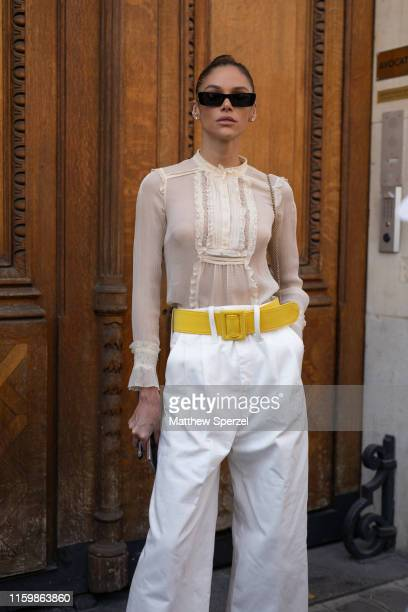 Guest is seen on the street during Paris Fashion Week Haute Couture wearing sheer shirt, yellow belt and white pants on July 03, 2019 in Paris,...