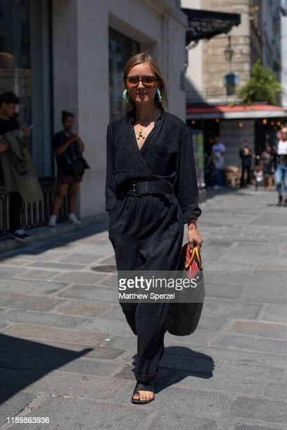 Guest is seen on the street during Paris Fashion Week Haute Couture wearing black outfit with black belt and bag on July 03, 2019 in Paris, France.
