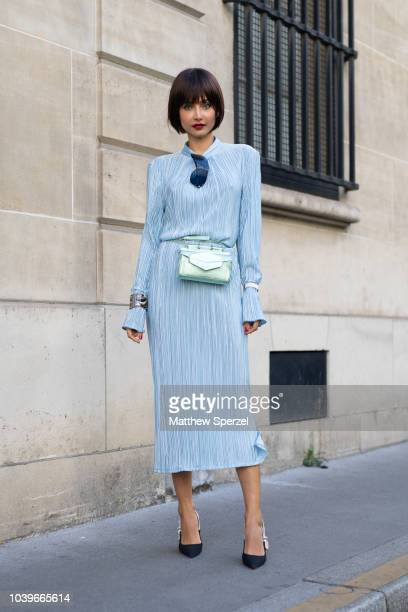 A guest is seen on the street during Paris Fashion Week SS19 wearing baby blue dress with pastel green hip belt bag and silver watch on September 24...