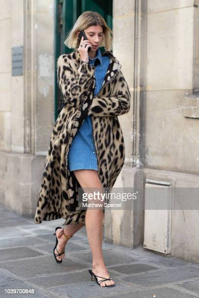 A guest is seen on the street during Paris Fashion Week SS19 wearing leopard print coat with blue denim dress on September 24 2018 in Paris France