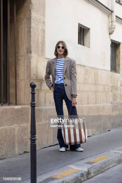 A guest is seen on the street during Paris Fashion Week SS19 wearing blue/white striped shirt with grey blazer and blue jeans on September 25 2018 in...