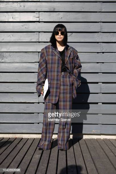 A guest is seen on the street during Paris Fashion Week SS19 wearing oversized brown plaid suit on September 25 2018 in Paris France