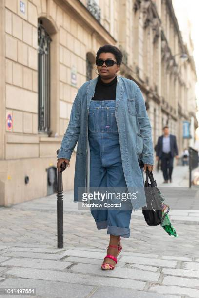 A guest is seen on the street during Paris Fashion Week SS19 wearing denim overalls and jacket with pink shoes on September 26 2018 in Paris France