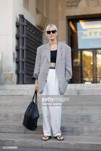 A guest is seen on the street during Paris Fashion Week SS19 wearing oversized grey blazer with black crop top and white pants on September 27 2018...
