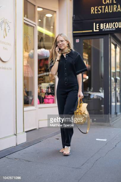 Guest is seen on the street during Paris Fashion Week SS19 wearing navy jumpsuit with yellow bag on September 27, 2018 in Paris, France.
