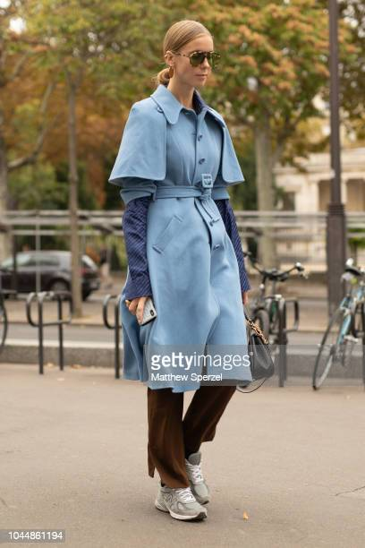 A guest is seen on the street during Paris Fashion Week SS19 wearing baby blue coat with brown pants on October 2 2018 in Paris France