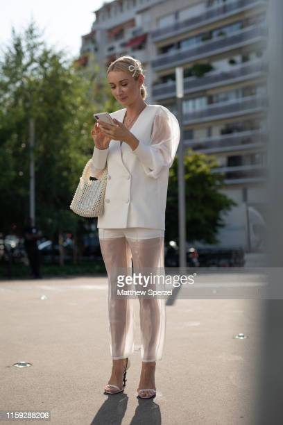 Guest is seen on the street during Paris Haute Couture Fashion Week wearing white vest, sheer shirt and pants on June 30, 2019 in Paris, France.
