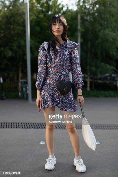 Guest is seen on the street during Paris Haute Couture Fashion Week wearing navy floral pattern dress with black heart shaped bag and white sneakers...