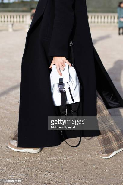 A guest is seen on the street during Paris Men's Fashion Week carrying Alyx white bag on January 16 2019 in Paris France