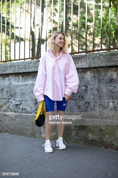 A guest is seen on the street during Paris Men's Fashion Week S/S 2019 wearing a pink oversized shirt with blue spandex shorts on June 20 2018 in...