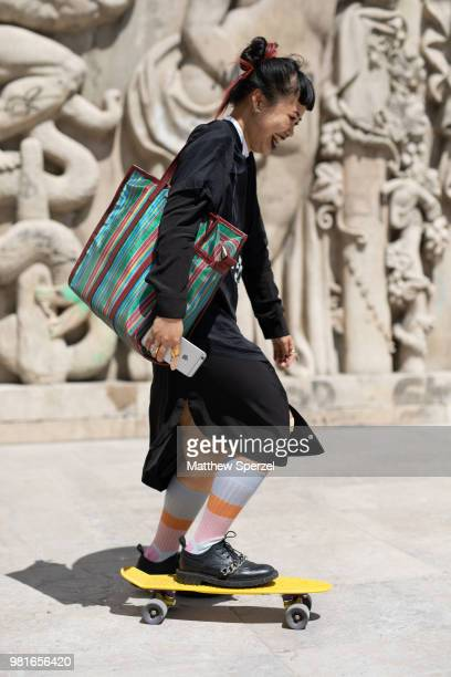 A guest is seen on the street during Paris Men's Fashion Week S/S 2019 wearing a black outfit with green bag and yellow skateboard on June 22 2018 in...