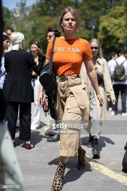 A guest is seen on the street during Paris Men's Fashion Week S/S 2019 wearing an orange shirt with khaki cargo pants and animal print shoes on June...