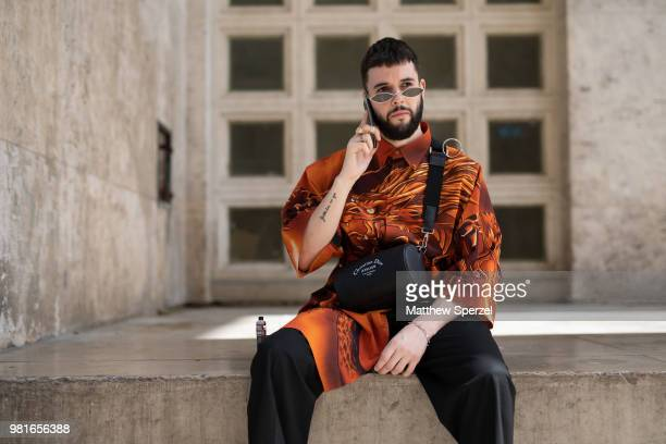 A guest is seen on the street during Paris Men's Fashion Week S/S 2019 wearing an orange/black outfit with crossbody bag on June 22 2018 in Paris...