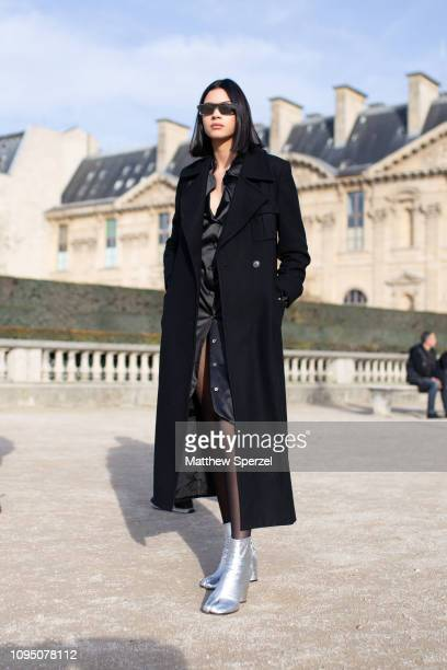 A guest is seen on the street during Paris Men's Fashion Week wearing black silk dress with black wool coat and silver boots on January 16 2019 in...