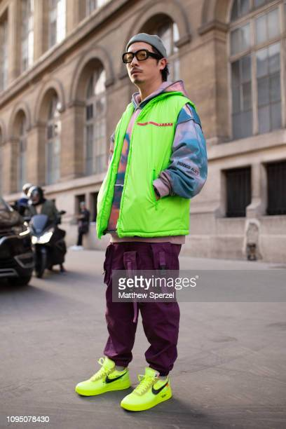 A guest is seen on the street during Paris Men's Fashion Week wearing neon vest and shoes with merlot pants and grey beret on January 16 2019 in...