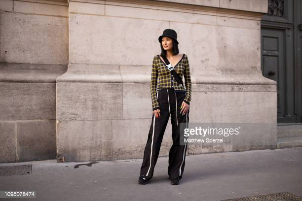 A guest is seen on the street during Paris Men's Fashion Week wearing yellow grid pattern shirt Alyx crossbody bag black with white stripe pants and...