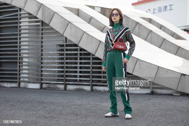 A guest is seen on the street during Shanghai Fashion Week SS19 wearing green argyle sweater with brown shoulder bag and green track pants on October...
