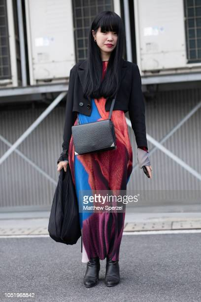 A guest is seen on the street during Shanghai Fashion Week SS19 wearing black blazer with orange/blue dress and black leather shoulder bag and shoes...