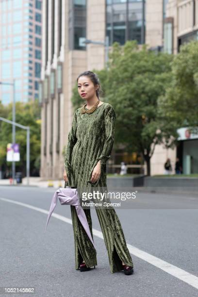 Guest is seen on the street during Shanghai Fashion Week SS19 wearing dark green pantsuit with silver bag on October 14, 2018 in Shanghai, China.
