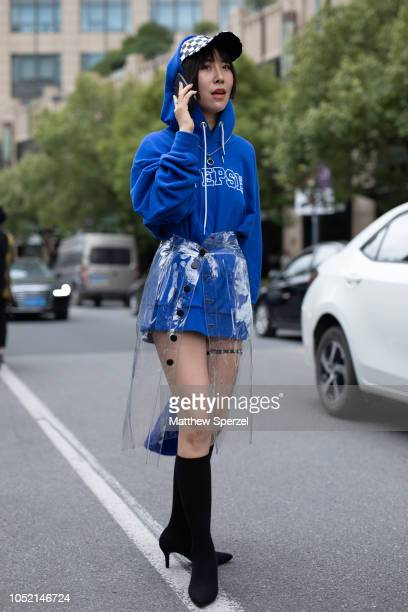 A guest is seen on the street during Shanghai Fashion Week SS19 wearing blue hoodie and bag with PVC skirt checker hat and black kneehigh shoes on...