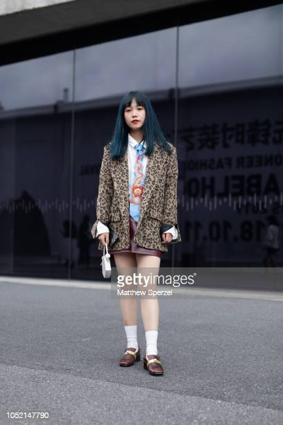 Guest is seen on the street during Shanghai Fashion Week SS19 wearing leopard print blazer, colorful dragon necktie, white shirt, maroon skirt, and...