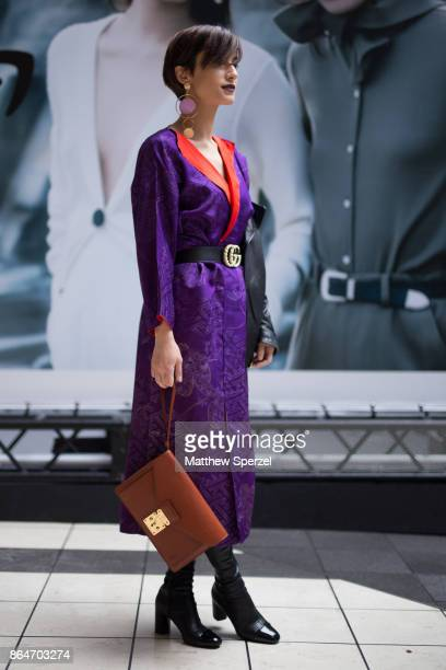 A guest is seen on the street during Tokyo Fashion Week wearing a purple and red dress with brown bag on October 21 2017 in Tokyo Japan