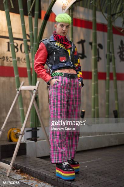 A guest is seen on the street during Tokyo Fashion Week wearing a leather jacet with pink plaid pants and rainbow platform shoes on October 21 2017...
