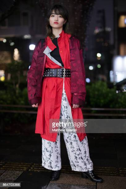 A guest is seen on the street during Tokyo Fashion Week wearing a red coat with wide black leather belt and Japanese character print pants on October...