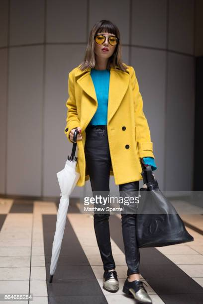 A guest is seen on the street during Tokyo Fashion Week wearing a teal sweater with yellow coat and black pants on October 21 2017 in Tokyo Japan