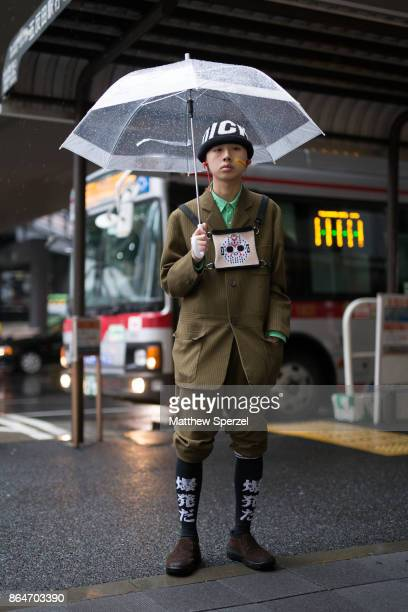 A guest is seen on the street during Tokyo Fashion Week wearing an army green suit with kneehigh socks and hockey mask design bat strapped on his...