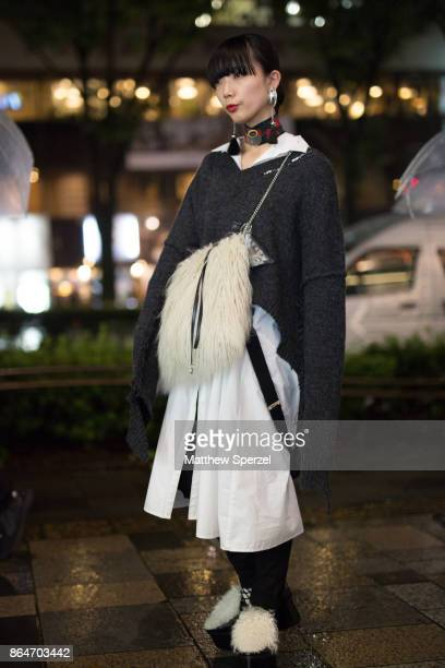 A guest is seen on the street during Tokyo Fashion Week wearing an oversized grey sweater with fur bag and shoes on October 21 2017 in Tokyo Japan